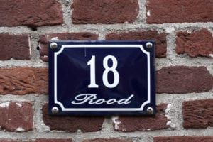 Enameled house number eighteen on a red brick wall